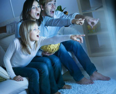 A family watching a bright TV at night on the sofa