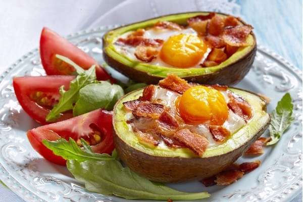 Plate of avocado with a fried egg and bacon in it