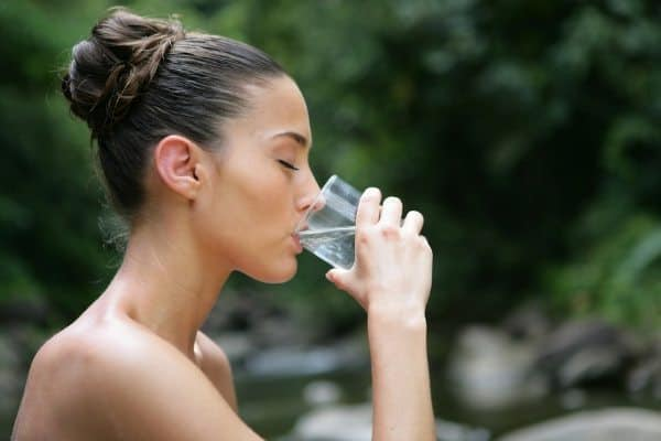 Young woman drinking water from a glass outside by a stream