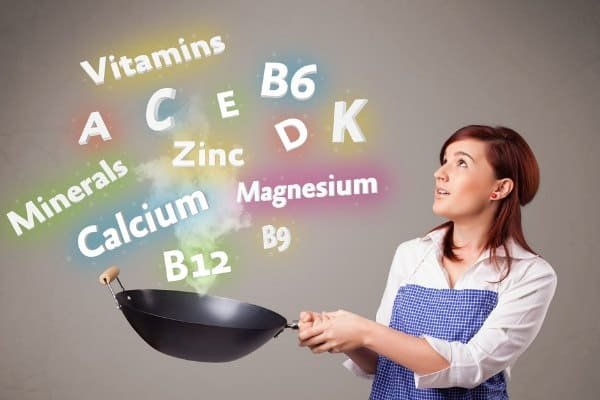 Women with a pan looking at common names for vitamins and minerals