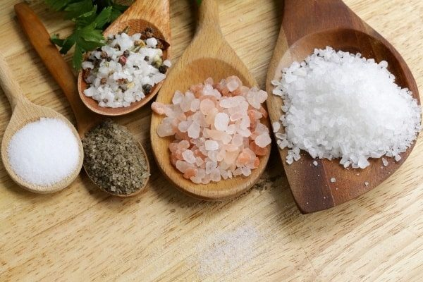 Different natural salts on wooden spoons