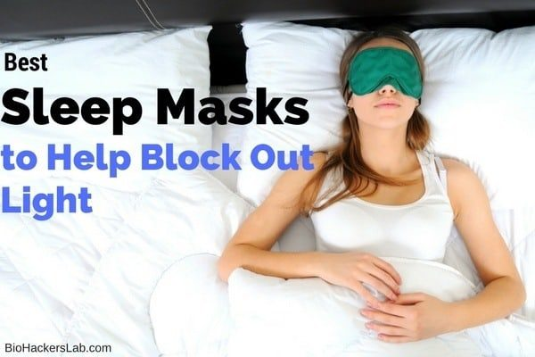 Woman sleeping on her back wearing a large eye mask in bed