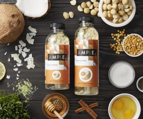 Small and large bottles of Ample K on a wooden table with natural ingredients